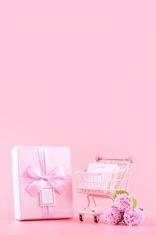 Concetto di design del regalo di festa della festa della mamma, bouquet di fiori di garofano rosa con scatola avvolta, carrello della spesa, borsa, isolato su sfondo rosa chiaro, spazio di copia.