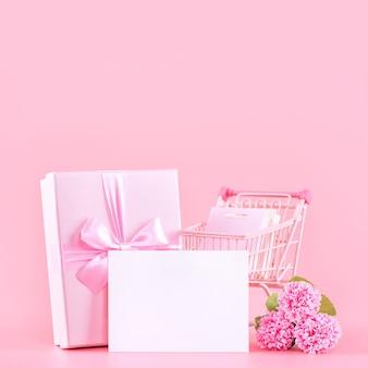 Concetto di progetto del regalo di festa di festa della mamma, bouquet di fiori di garofano rosa con confezione regalo avvolta isolato su sfondo rosa, spazio di copia.