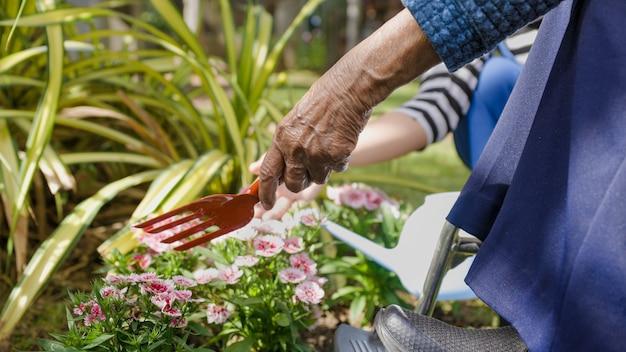 Festa della mamma, donna anziana e figlia si rilassano con il giardinaggio in cortile