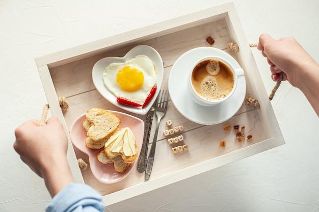 Festa della mamma. sul vassoio c'è una tazza di caffè, due piatti di uova strapazzate e pane a forma di cuore e la scritta i love you mom. vista dall'alto.