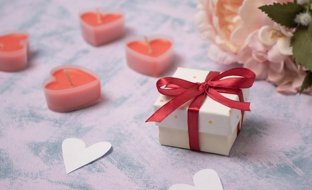 La festa della mamma, il giorno di san valentino o il concetto di natale. con un regalo rosso e uno sfondo con luci