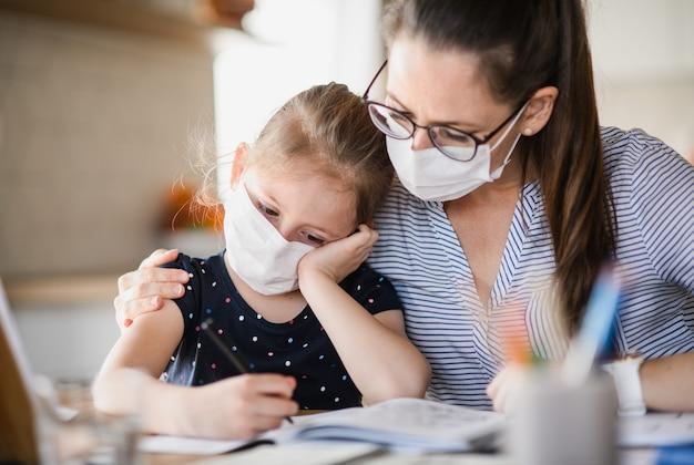 Madre e figlia triste con maschere facciali che imparano in casa a casa, virus corona e concetto di quarantena.