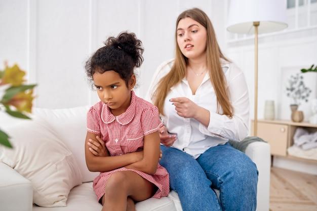 La madre rimprovera la sua piccola figlia sul divano in soggiorno