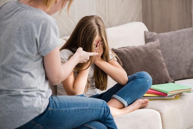 La madre rimprovera la figlia piangente della scuola per i compiti