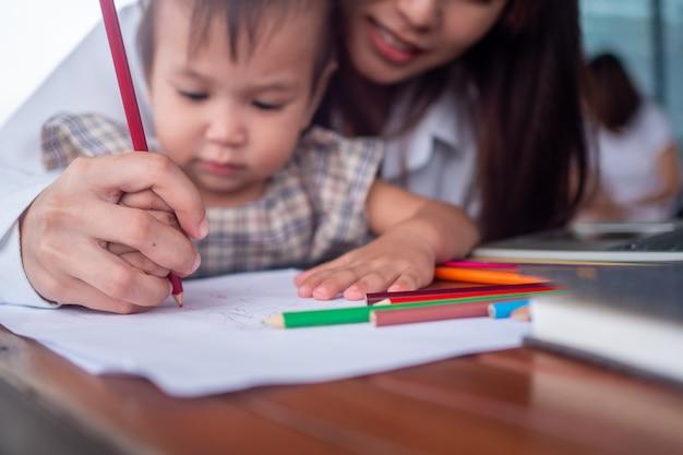 La madre stringe la mano a sua figlia per insegnarti come dipingere o fare i compiti allegramente. la giovane insegnante femminile insegna ai bambini nell'aula dell'asilo con gioia e relax.