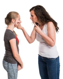 Madre che grida a sua figlia adolescente su un muro bianco