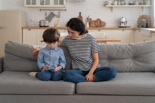 Madre che si siede sul divano con il ragazzino guarda cartoni animati, video su smartphone. felice famiglia amorevole.