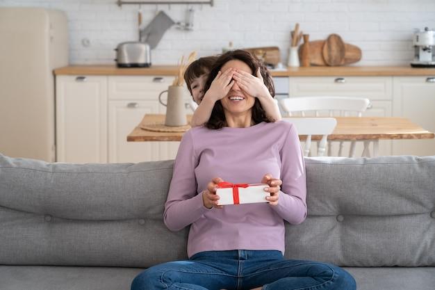Madre seduta sul divano a casa bambino che copre gli occhi della madre congratulandosi e dando un regalo a sorpresa