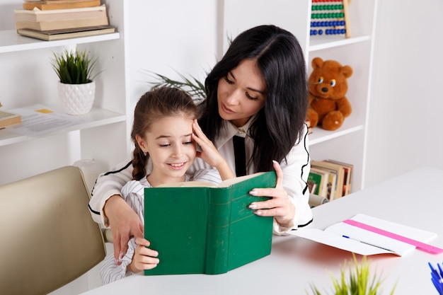 Madre seduta con la bambina e insegnandole a leggere.