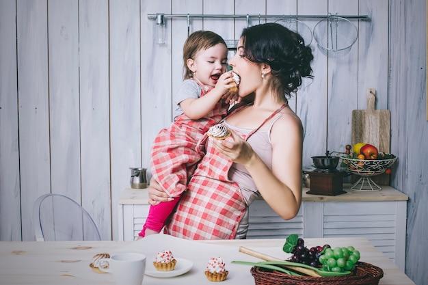 Madre e bambino piccolo in cucina a casa con grembiuli