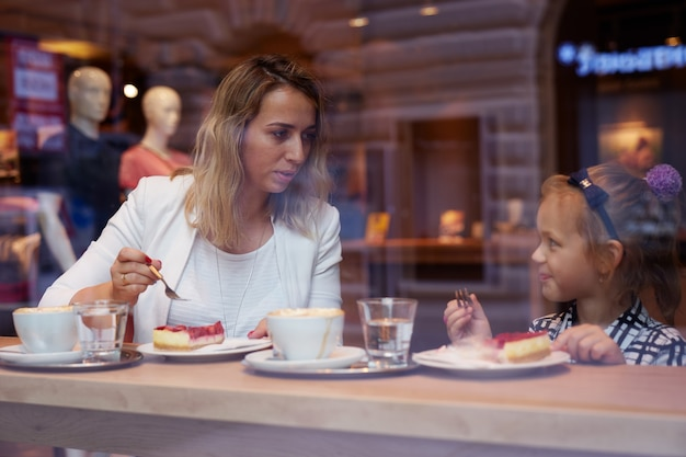 Madre e figlia piccola che mangiano torta nella caffetteria