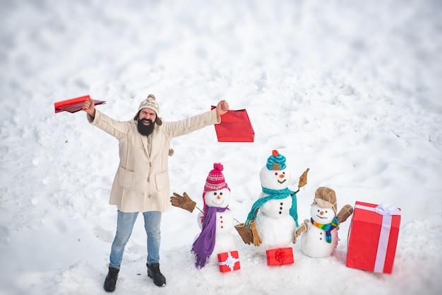 Mamma pupazzo di neve, padre pupazzo di neve e bambino augurano buon natale e felice anno nuovo. buon pupazzo di neve