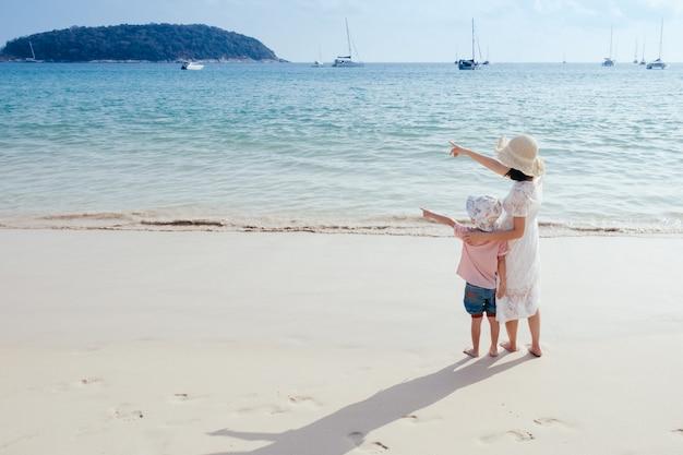 Una madre e un figlio sulla spiaggia all'aperto mare e cielo blu