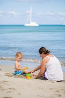 Madre e figlio costruiscono un castello di sabbia sulla spiaggia