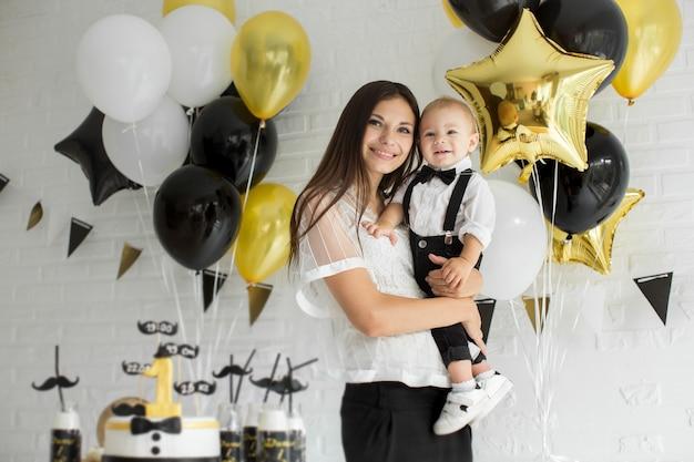 Madre e figlio che festeggiano il primo compleanno insieme ridendo e sorridendo con palloncini, una barretta di cioccolato.