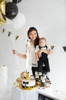 Madre e figlio festeggiano il 1 ° compleanno insieme ridendo e sorridendo con palloncini
