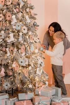 Madre e figlio che decorano il concetto dell'albero di natale
