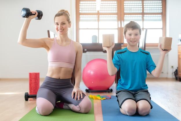 Madre e figlio che fanno allenamento con i pesi a casa durante il coprifuoco di blocco