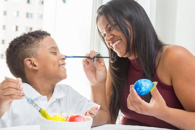 Madre e figlio divertendosi a dipingere l'uovo di pasqua.