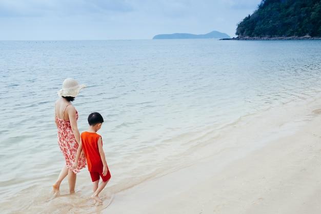Una madre e figlio tenendo la mano e camminando sulla spiaggia e mare all'aperto al tramonto