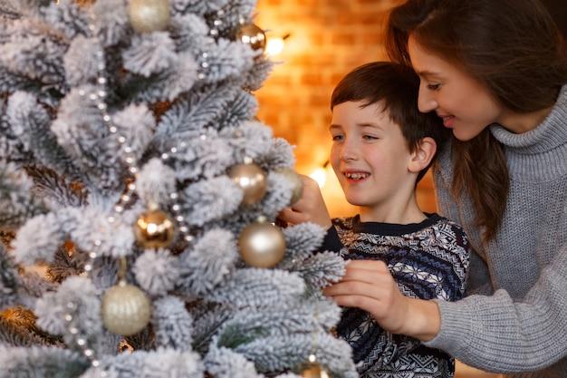 Madre e figlio a casa che decorano un albero di natale