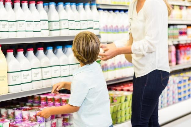 Madre e figlio guardando il frigo del supermercato