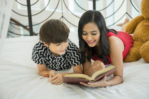 Madre e figlio che si trovano sul letto a leggere un libro