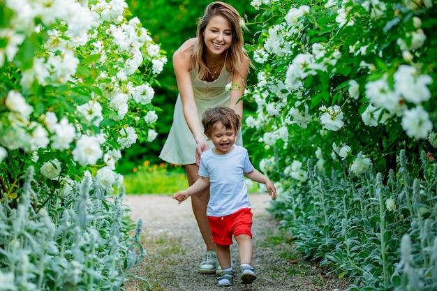 Madre e figlio vicino a rose bianche in un giardino in primavera