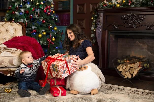 Madre e figlio aprono i regali di natale sul tappeto vicino all'albero di natale e al camino.