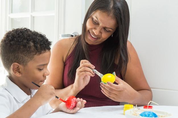 Madre e figlio che dipingono l'uovo di pasqua.