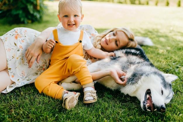 Madre e figlio in posa con un cane sull'erba