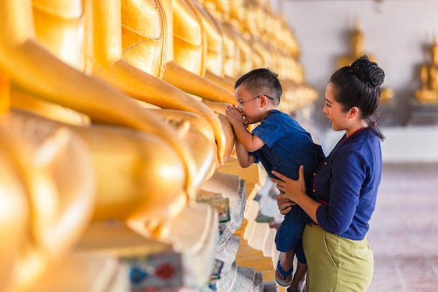 Madre e figlio che pregano rispetto statua del buddha in wat phutthai sawan temple, ayutthaya, thailandia. concetto di cultura tailandese