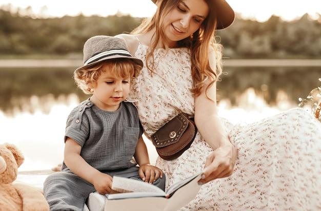 Libro di lettura di madre e figlio vicino al lago