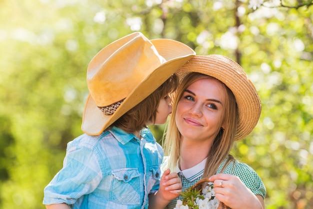 Madre e figlio in cappello di paglia. felice giornata in famiglia. festa della mamma. piccolo ragazzo ama la mamma. vacanze estive. madre e bambino si rilassano nel parco. picnic con fioritura primaverile nel cestino.