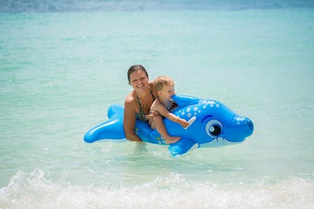 Madre e figlio nuotano nell'oceano su un delfino gonfiabile