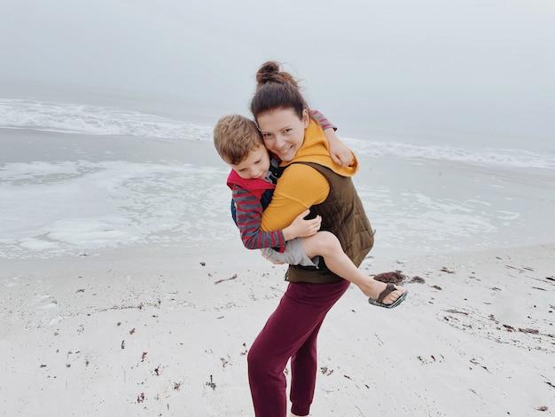 Madre e figlio camminano lungo la spiaggia nebbiosa e scattano una foto al telefono. ritratto di felice mamma e bambino ragazzo di tempo nuvoloso realizzato con il telefono. tempo in famiglia insieme.