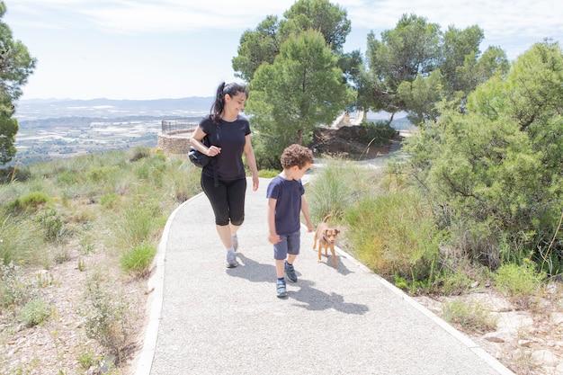 Madre e figlio che camminano felici e sorridenti con il cagnolino su un sentiero nella natura nel bush