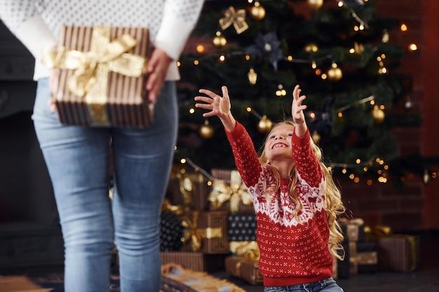 Madre in piedi con scatola regalo e fa una sorpresa per la figlia in casa durante le vacanze di natale.
