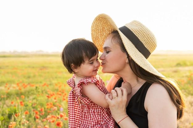 Madre in cappello di paglia con la figlia bambina in braccio nel campo di papaveri al tramonto