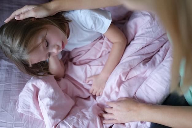Madre che accarezza la testa della bambina triste sdraiata a letto