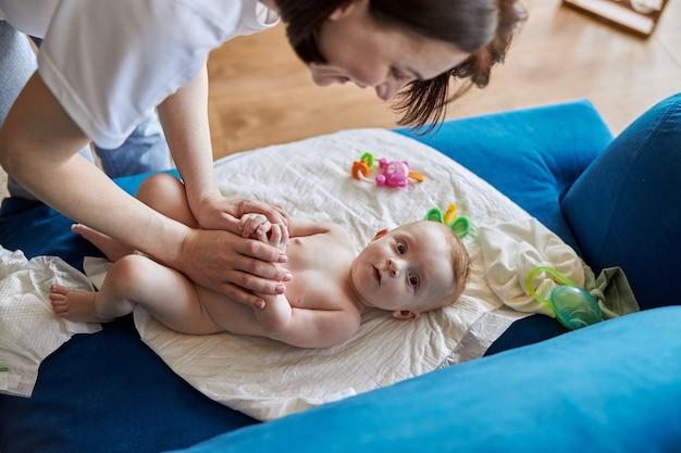 Madre che fascia il suo neonato su underpad sul divano. vista dall'alto del bambino neonato. giovane donna europea sorridente. interno dell'appartamento piatto. concetto di maternità e cura del bambino
