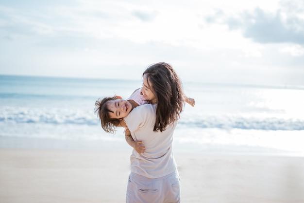 Madre che fa oscillare la figlia del bambino che gioca in spiaggia
