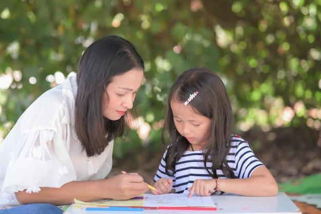 La madre insegna ai bambini asiatici della figlia che fanno i compiti della scuola nel giardino di casa o nel parco, concetto della scuola domestica.