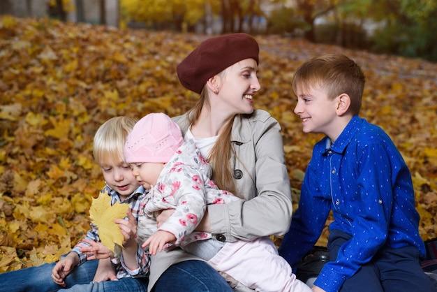 Madre e tre figli nel parco d'autunno. grande famiglia felice. fratelli.