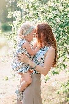 Madre che tocca il naso con la figlia felice in un meleto in fiore. foto di alta qualità