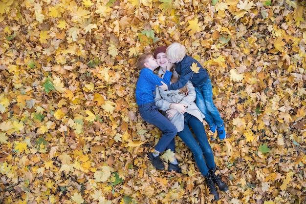 Madre e due bambini sdraiati in un grande mucchio di foglie. i figli baciano la mamma. vista dall'alto.