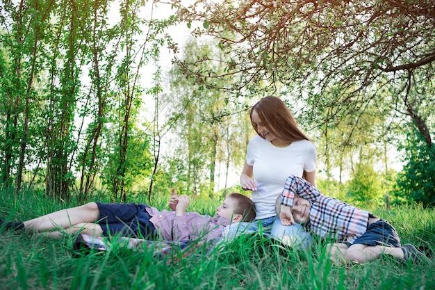 Madre e due bambini in picnic nel parco. infanzia di maternità spensierata.