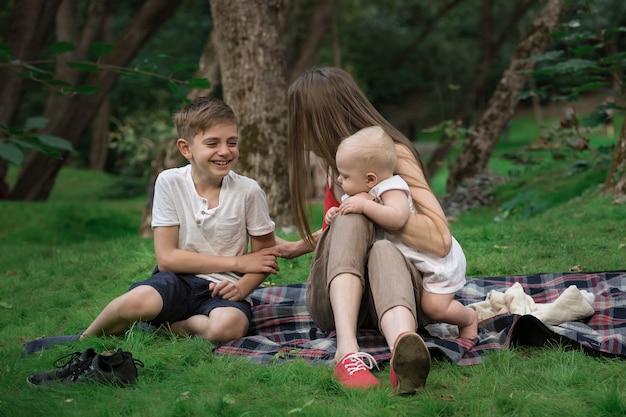 La madre e due bambini riposano nel parco. picnic in famiglia in giardino all'aperto.