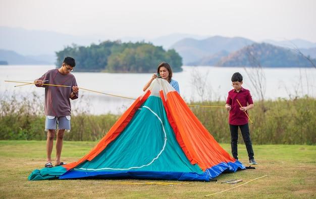Una madre e due figli si uniscono per montare una tenda per il campeggio in riva all'ampio lago. l'idea per l'avventura di attività all'aperto in famiglia in una vacanza.