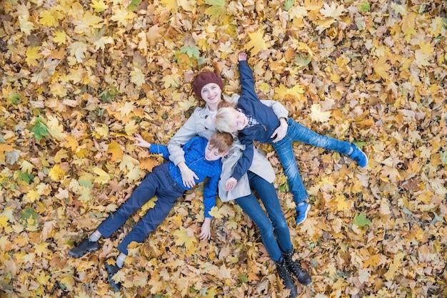 Madre e due figli sdraiati sul fogliame autunnale nella foresta. giovane famiglia nel parco. vista dall'alto.